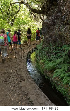 MADEIRA, PORTUGAL - SEPTEMBER 6, 2016: Tourist is walking along irrigation canals. Historic water supply system known as Levada in tropical forest Madeira Island Portugal