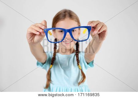 Little girl with spectacles on light background