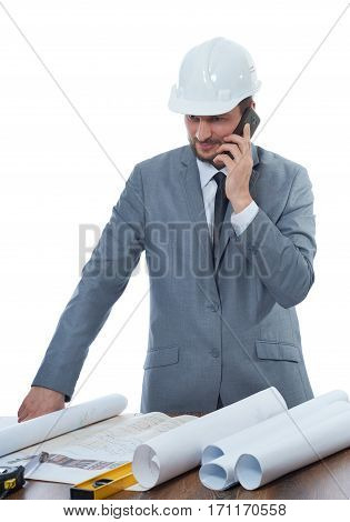 Portrait of architect in gray suite and safety hat reading architecture plan of building. Engineer talking on call phone, smiling at work place, table and many tools near.