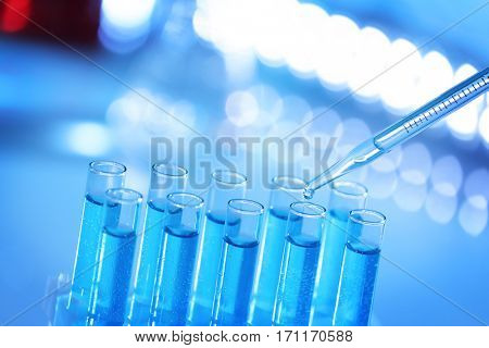 Pipette dropping sample into test tube on blurred background