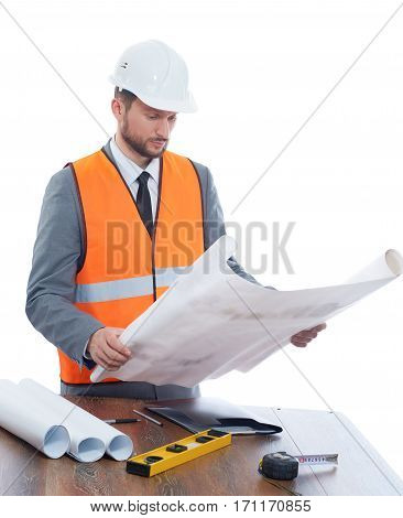 Engineer wearing in orange vest, suite and white safety hat holding big drawing plan. Male with beard reading architecture plan of building. Isolate on white background.