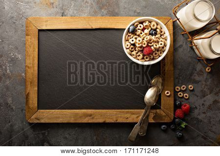 Healthy cold cereal with raspberry and blueberry in a bowl background with chalkboard overhead shot