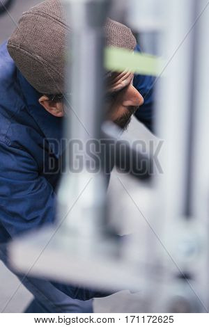Close-up of bearded man in cap working with metal.Unfocused bars on foreground