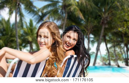 summer holidays, people, leisure, vacation and travel concept - happy women sunbathing in chairs over exotic tropical beach with palm trees and pool background