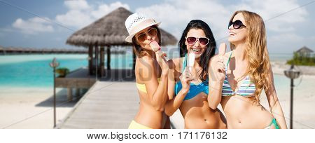 summer holidays, vacation, food, travel and people concept - group of smiling young women eating ice cream over exotic tropical beach with bungalow shed background
