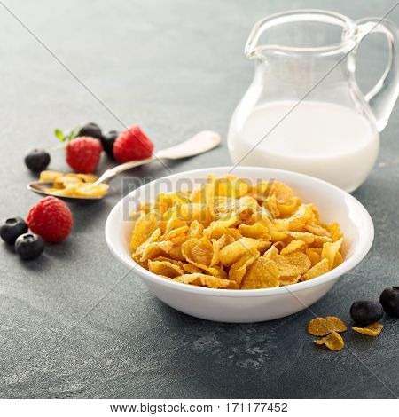 Cornflake cereals in a bowl with milk on blue background, quick breakfast