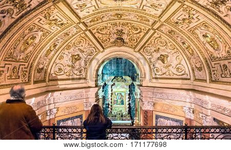 Turin, Italy - January 2, 2016: Interior of Santuario della Consolata with woman praying in Turin Italy. It is a prominent Marian sanctuary and minor basilica in central Turin Piedmont Italy.