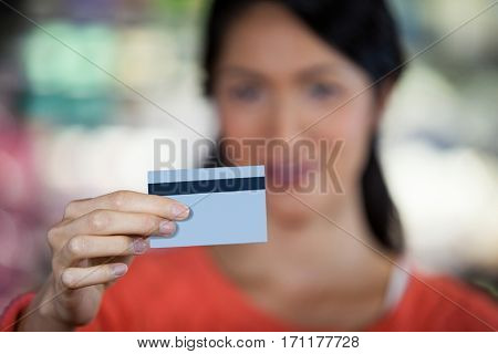 Close-up of woman holding credit card in supermarket