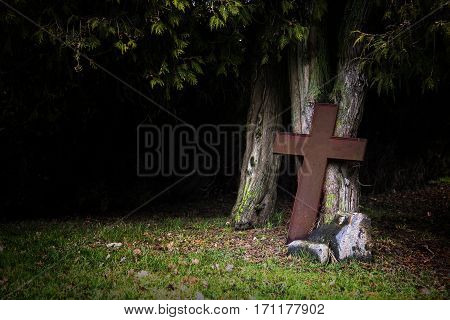 Rusty cross made of metal leaning against old tree trunks in shadow under the tops religious christian symbol for death Good Friday and Easter or creepy halloween concep