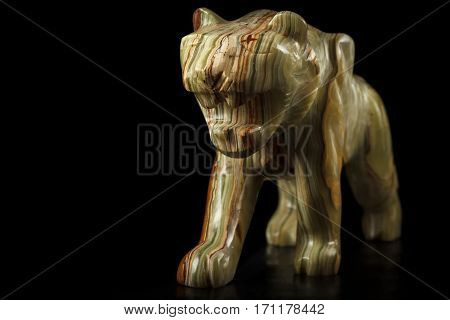 Onyx stone figure of a tiger on a black background. Front view