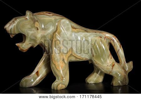 Onyx stone figure of a tiger on a black background. Side view