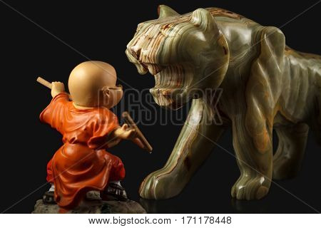 Little toy brave boy figure practicing martial arts in front of onyx stone figure of a tiger on a black background.