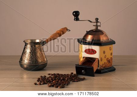 Coffee grinder cezve and coffee beans on wooden table
