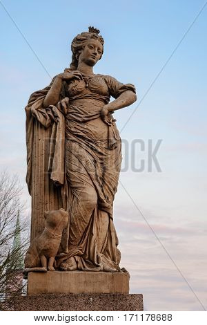 Freedom figure allegorical sculpture from sandstone from the 18th century on the doll bridge called Puppenbruecke in Luebeck tourist attraction in north germany copy space in the blue sky vertical