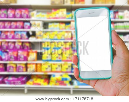 right hand holding green blank screen mobile phone with supermarket blur background online shopping concept