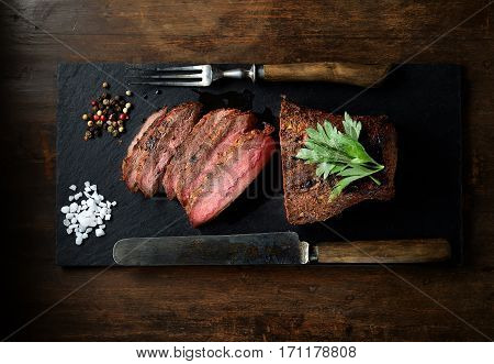 grilled steak on a black slate, knife and fork. Top view.