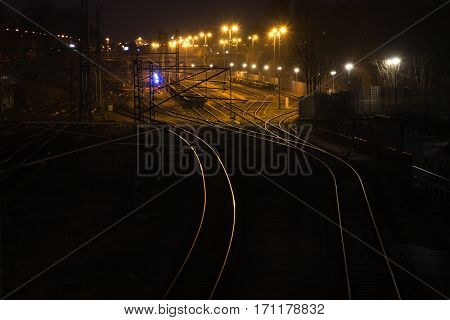 railway tracks at night lead shiny and curving to a cargo freight station copy space in the dark background selected focus