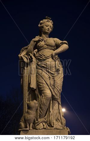 Freedom figure at night allegorical sculpture from sandstone from the 18th century on the doll bridge called Puppenbruecke in Luebeck tourist attraction in north germany copy space in the dark sky