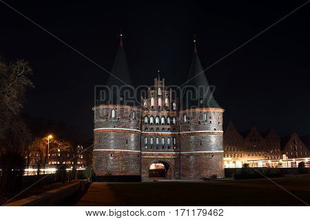 Holstentor in Luebeck at night iluminated agaist the dark sky the medieval city gate is a popular tourist attraction of the historic old town in Schleswig-Holstein Germany