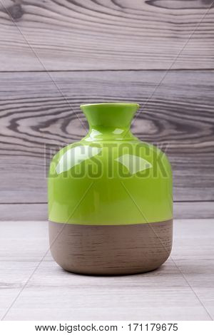 Bicolor vase on wooden background. Ceramic enameled vase. Design of combined colors vase. Handmade modern vase.