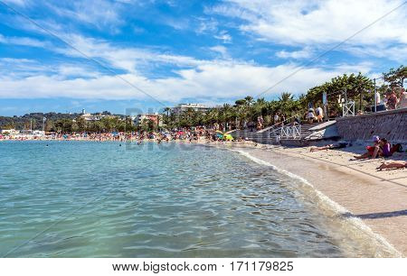 Antibes, France - June 26, 2016: people subathing on Plage du Ponteil in Antibes. Located between old Antibes and Cap d'Antibes it is a popular local beach a kilometre long curve of silky white sand.