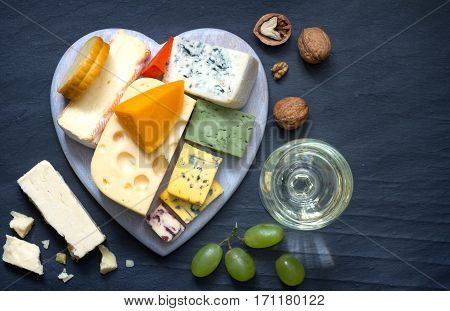 Various types of cheese on heart with glass of wine on black marble background