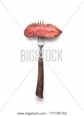 Slices of Medium rare grilled Steak Ribeye on meat fork on white background