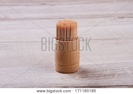 Wooden toothpicks in box. Toothpicks on wooden background. Floss your teeth after meal. Importance of mouth hygiene.
