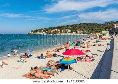 Antibes, France - June 26, 2016: people subathing on Plage de la Salis in Antibes. It is a popular local beach a long stretch of fine white sand curving around a protected bay.