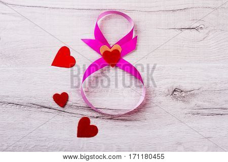 Ribbon in shape of 8. Hearts on wooden surface. Imagination without borders. Example of holiday handmade.