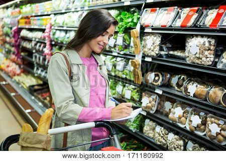 Woman writing on notepad while shopping for vegetables in grocery section at supermarket