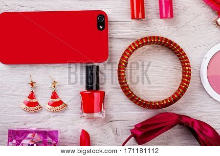 Cell phone, make-up, accessories. Bracelet and earrings near perfume. Construct your stylish look. Expression through fashion.
