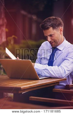 Happy businessman using laptop and digital tablet at sidewalk cafe