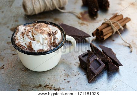 Enamel mug of hot chocolate cocoa with whipped cream slice of bitter chocolate and cinnamon sticks on vintage metal background. Winter times drink concept. Delicious cold weather beverage.
