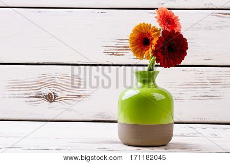 Gerberas in ceramic vase. Enameled vase with flowers. Greet your lady with flowers. Perfect decorative element of interior.