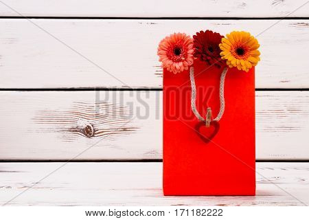 Heart on paper bag. Gerbera flowers in red bag. Lovely packed flowers as present. Be romantic and spread love.