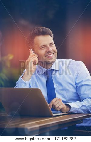 Cheerful businessman talking on mobile phone while using laptop at sidewalk cafe