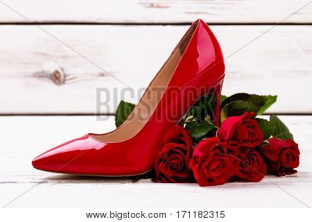 Red heel shoe and roses. Flowers and footwear on wood.. Gift with taste.