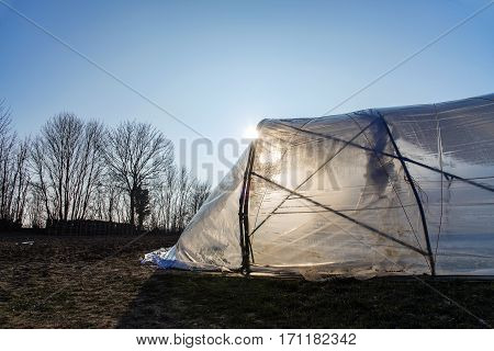 Greenhouse tunnel from polythene plastic backlit by the sun on an agricultural field rural landscape with blue sky copy space