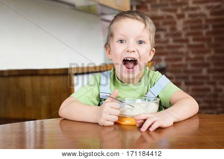 Five years boy eats, opened his mouth and shouts rice porridge on the kitchen