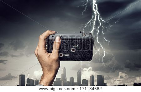 Man taking photo with vintage camera . Mixed media