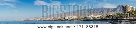 COSTA ADEJE SPAIN - JANUARY 17 2016: Panoramic view on coastline of famous Tenerife resort. Mountains and El Teide volcano on background.