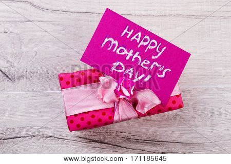 Mother's Day card and present. Pink gift with bow. Surprise for beloved mother. Lovely handmade present.