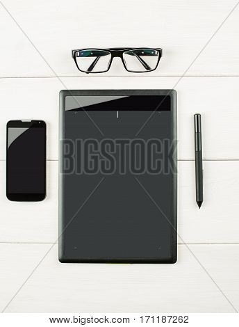 Graphic Tablet With Eyeglasses And Smartphone On A White Wooden Table, Vertical