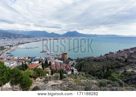 Panorama of Alanya Mediterranean town of Turkey showing sea mountains Red Tower and castle walls shot on gloomy day
