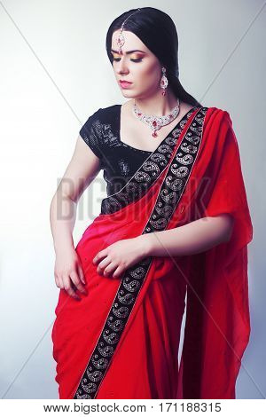 portrait of indian woman greeting somebody in red sari isolated on white background in photostudio