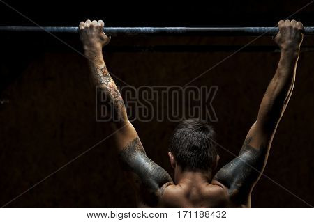 Cropped shot of muscular strong man doing pull up exercise on horizontal bar in gym. fitness, gymnastics workout.