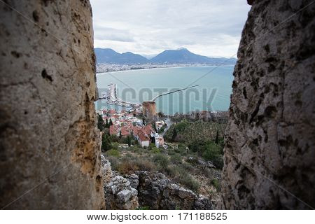 View of Alanya Mediterranean town of Turkey between castle walls showing sea mountains Red Tower shot on gloomy day