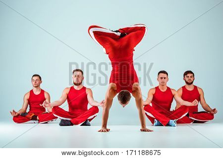 The group of gymnastic acrobatic caucasian men posing in balance posture on gray studio background