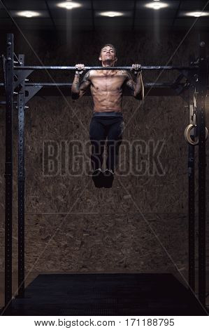 Strong muscular young man pulling up on horizontal bar. Fitness, gymnastics workout.